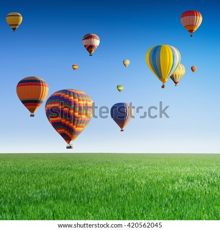 Hot air balloons flying in clear blue sky above green grass field - stock photo