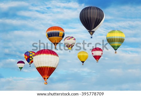Hot Air Balloons Flying In Cloudy Blue Sky.