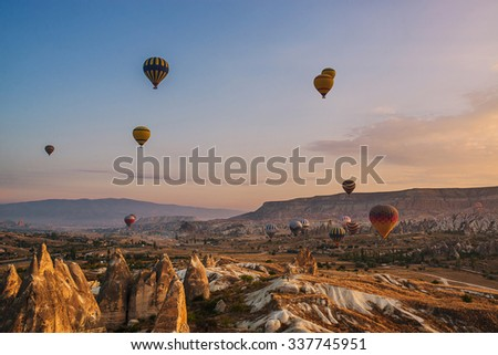 Hot air balloons flying  in the sunrise over mountain landscape at Cappadocia, Turkey - stock photo
