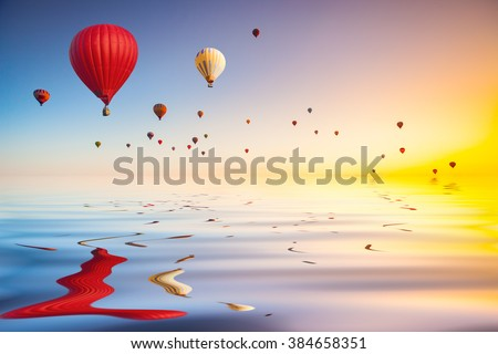 hot air balloons in blue sky flying over water surface - stock photo
