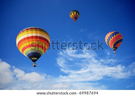 Hot-air balloons in the cloudy blue sky - stock photo