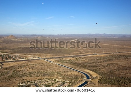 Hot Air Balloons over desert freeway and canal - stock photo