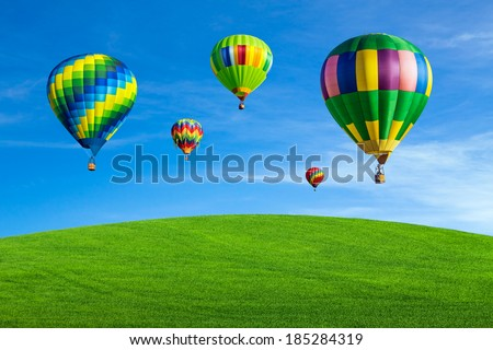 Hot air balloons over green field with blue sky - stock photo