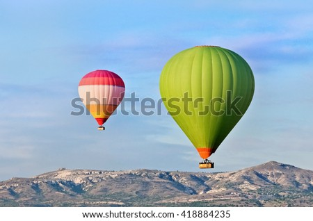 Hot air balloons over mountain landscape in Cappadocia, Goreme National Park, Turkey