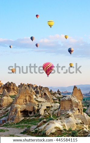 Hot air balloons over mountain landscape in Cappadocia, Goreme National Park Turkey.