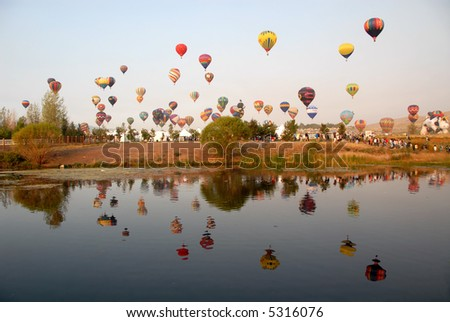 Hot air balloons reflected in a lake, Reno, Nevada - stock photo