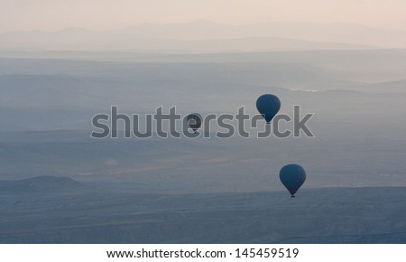 Hot air balloons rise over valley in Cappadocia, Turkey - stock photo