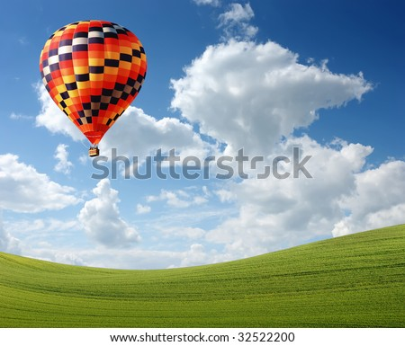 Hot air baloon floating in the sky over land - stock photo