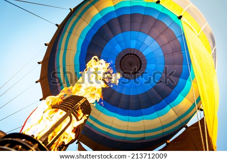 Hot air from a gas burner fills the dome of the balloon - stock photo