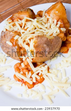 Hot and crispy baked potato stuffed with baked beans and grated cheese - stock photo