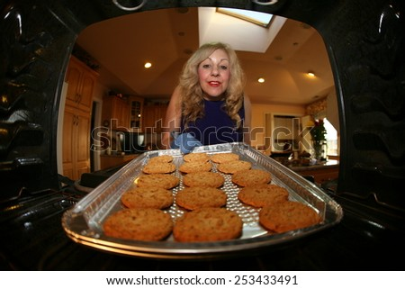 Hot and Fresh COOKIES right from the oven!  A lady bakes cookies for a charity bake sale to help raise money for a homeless people - stock photo