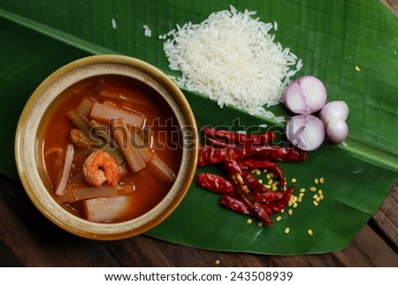 hot and sour, shrimp, banana stalk, and vegetable in the earthen jar showing with its ingredient of chili sauce. hot and sour taste of a kind of thai curry. Thai food. Thai curry. - stock photo