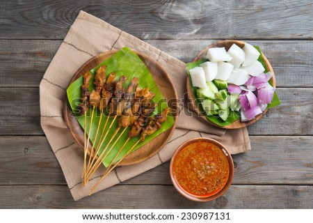 Hot and spicy Asian dish. Delicious chicken sate or satay, skewered and grilled meat, served with peanut sauce. Fresh cooked with steamed and smoke.  - stock photo