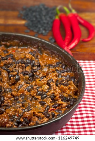 Hot and spicy Chili con Carne in the frying pan with rice. Whole red peppers and raw black beans in the background. - stock photo