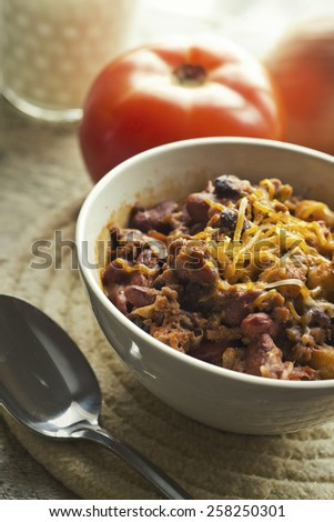 Hot and spicy Chili con carne with a glass of milk and pepper jack cheese - stock photo