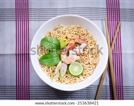 Hot and spicy instant noodle on the wood table.