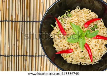 Hot and spicy instant noodle on wooden background - stock photo
