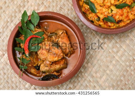 Hot and spicy popular Kerala fish curry, King fish curry and young jackfruit /  jakfruit  / jack / jak curry in earthen ware / clay / mud pot . South Indian dish