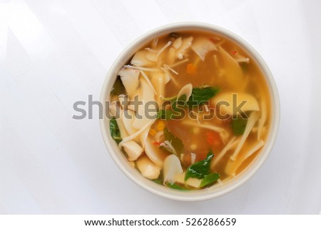 Hot and Spicy Soup with mushroom, mix vegetable and Thai herbs in white bowl on white background ,Vegetarian Food, Healthy food