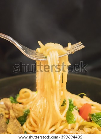 Hot and spicy spaghetti with fork over black background - stock photo