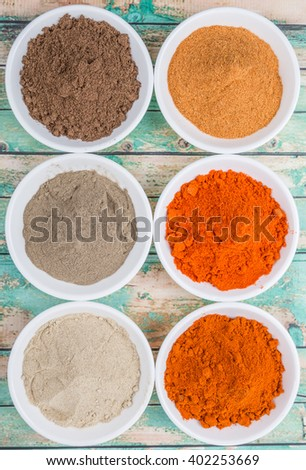 Hot and spicy spices powder, cayenne powder, chilly powder, peppercorn powder, paprika powder, black pepper and white pepper powder in white bowl over wooden background