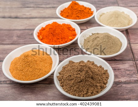 Hot and spicy spices powder, cayenne powder, chilly powder, peppercorn powder, paprika powder, black pepper and white pepper powder in white bowl over wooden background - stock photo