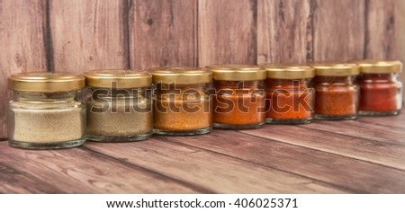 Hot and spicy spices powder, cayenne powder, chilly powder, peppercorn powder, paprika powder, black pepper and white pepper powder in small mason jar over wooden background - stock photo