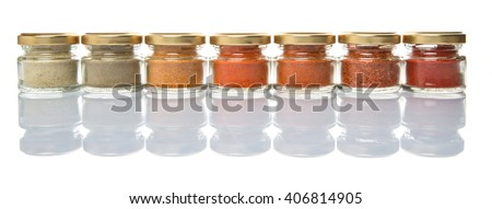 Hot and spicy spices powder, cayenne powder, chilly powder, peppercorn powder, paprika powder, black pepper and white pepper powder in small mason jar over white background