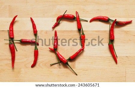 Hot and spicy word with red peppers - stock photo