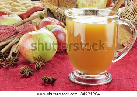 Hot apple cider with cinnamon bark, anise stars and fresh apples. Shallow depth of field with selective focus on cider. - stock photo