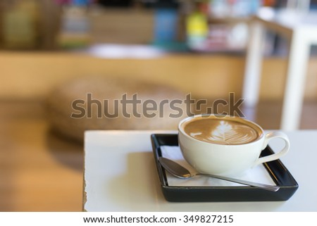 Hot art Latte Coffee in a cup and laptop on wooden table