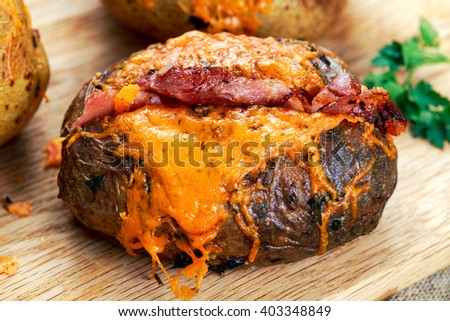 Hot Baked Potato with cheese, bacon and sour cream - stock photo