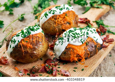 Hot Baked Potato with cheese, bacon, chives and sour cream - stock photo