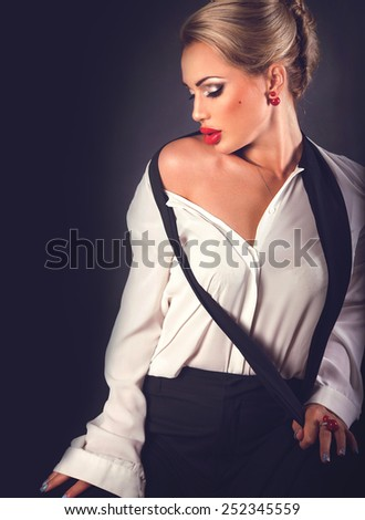 Hot beautiful blonde woman with red plump lips in black pants and white shirt sexy posing on dark background with copy space  - stock photo