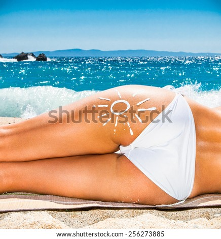 Hot beautiful woman with suntan loton sign in bikini lying on the beach. Greece. - stock photo