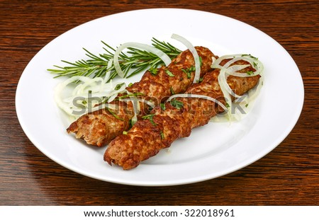 Hot Beef kebab with onion rings and rosemary - stock photo
