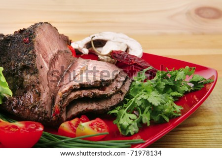 hot beef on red plate over wood table - stock photo