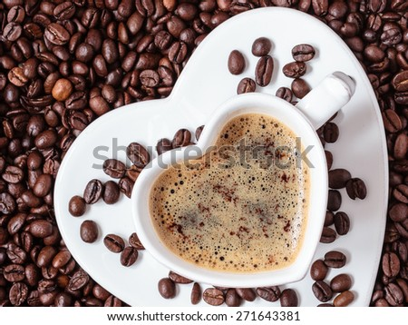 Hot beverage. White coffee cup heart shaped with cappucino latte on roasted beans background - stock photo