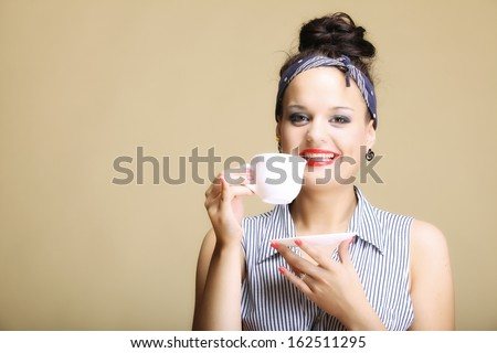 Hot beverage. Woman funny happy girl holding a cup of tea or coffee copyspace brown background - stock photo