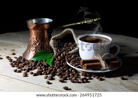 Hot Black Coffee in Coffee Pot and White Coffee Cup with Coffee Beans on Black Background - stock photo