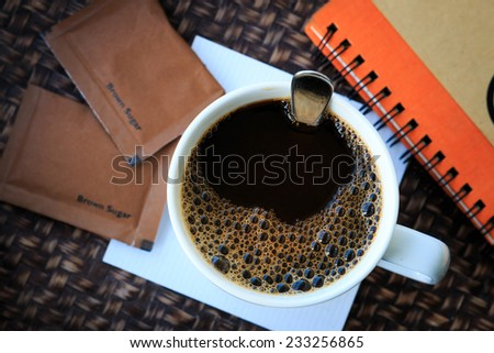 hot black coffee in white cup with brown sugar on tray. - stock photo