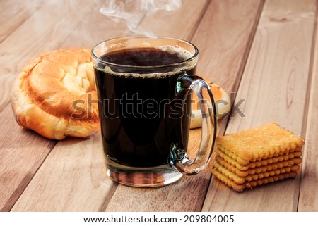 Hot Black Coffee with Bread on Wooden Table.
