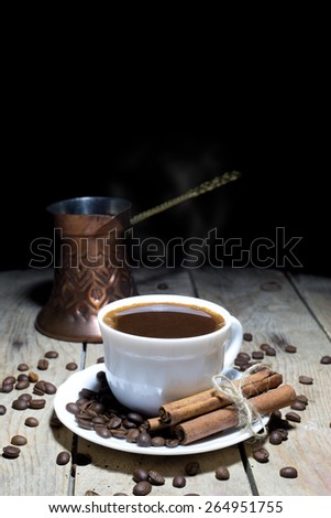 Hot Black Coffee with Coffee Beans, Cinnamon and Coffee Pot on Wooden Table, Black Background - stock photo