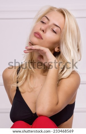 Hot blonde girl in red pants and bra posing in white room - stock photo