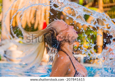 Hot blonde woman enjoying the swimming pool at the resort - stock photo
