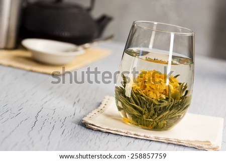 Hot Blooming Flower Tea with Teapot: as the water in the glass heats the ball of tea it opens into a flower - stock photo