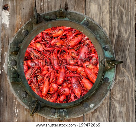 Hot boiled crawfish through a rustic old porthole - stock photo