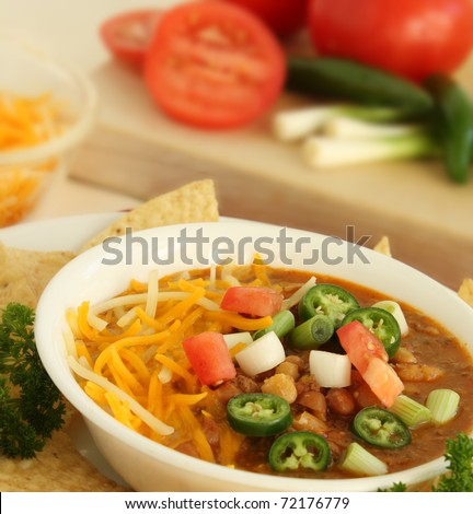 Hot bowl of Chili with green onions, tomatoes, jalapenos and cheese - stock photo