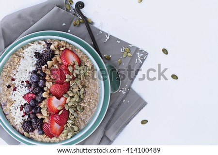 Hot breakfast of healthy oatmeal with shredded coconut, blackberries, blueberries, walnuts, heart shaped strawberries and pumpkin seeds over a white background. Image shot from overhead.