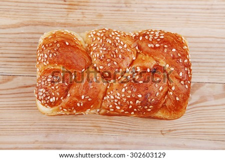 hot bun of light wheat bread topped by sesame seeds on wood - stock photo